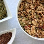 granola with pumpkin seeds, almonds, pecans and flax seeds in a bowl