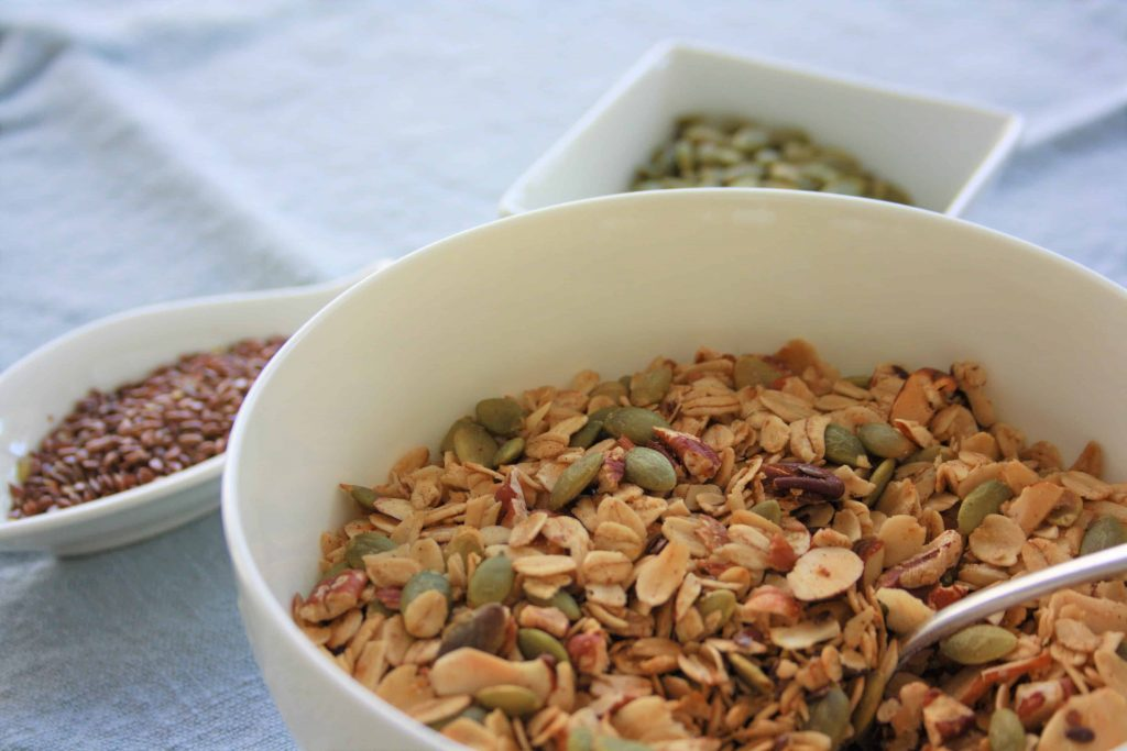 granola with pumpkin seeds, almonds, pecans and flax seed in a bowl