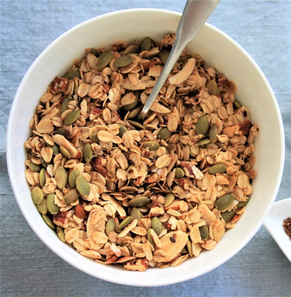 crunchy granola with pecans, pumpkin seeds, almonds and flax seeds in a round bowl with a spoon in it