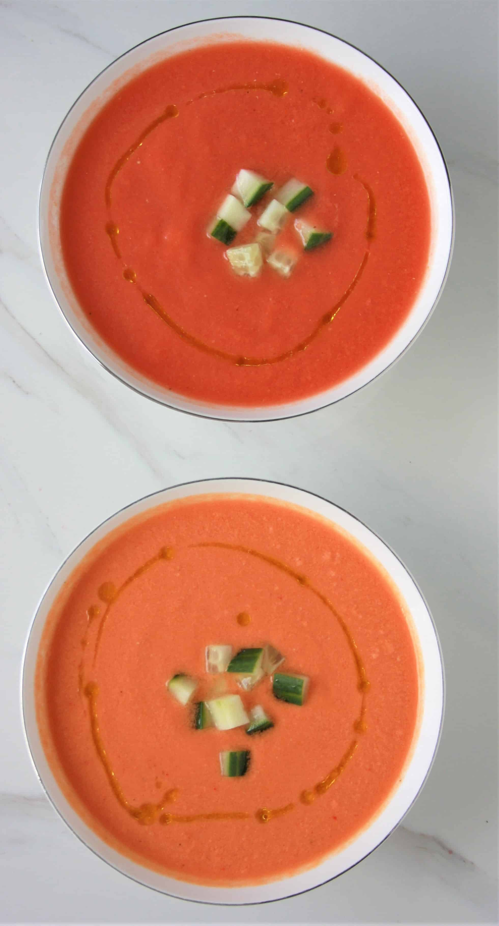 red and orange gazpacho in two bowls with diced cucumber on top and sprinkled olive oil