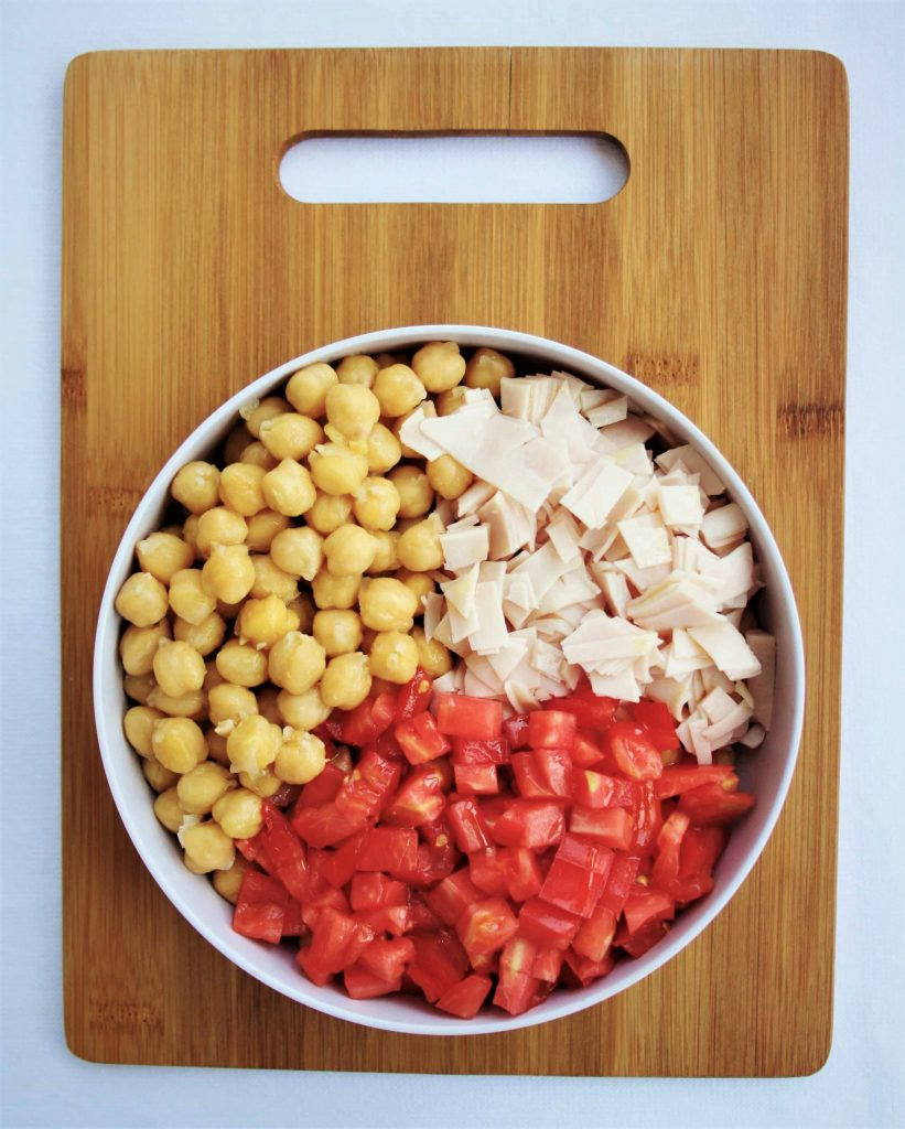 chickpeas, tomatoes, turkey breast in a bowl on a  wooden cutting board