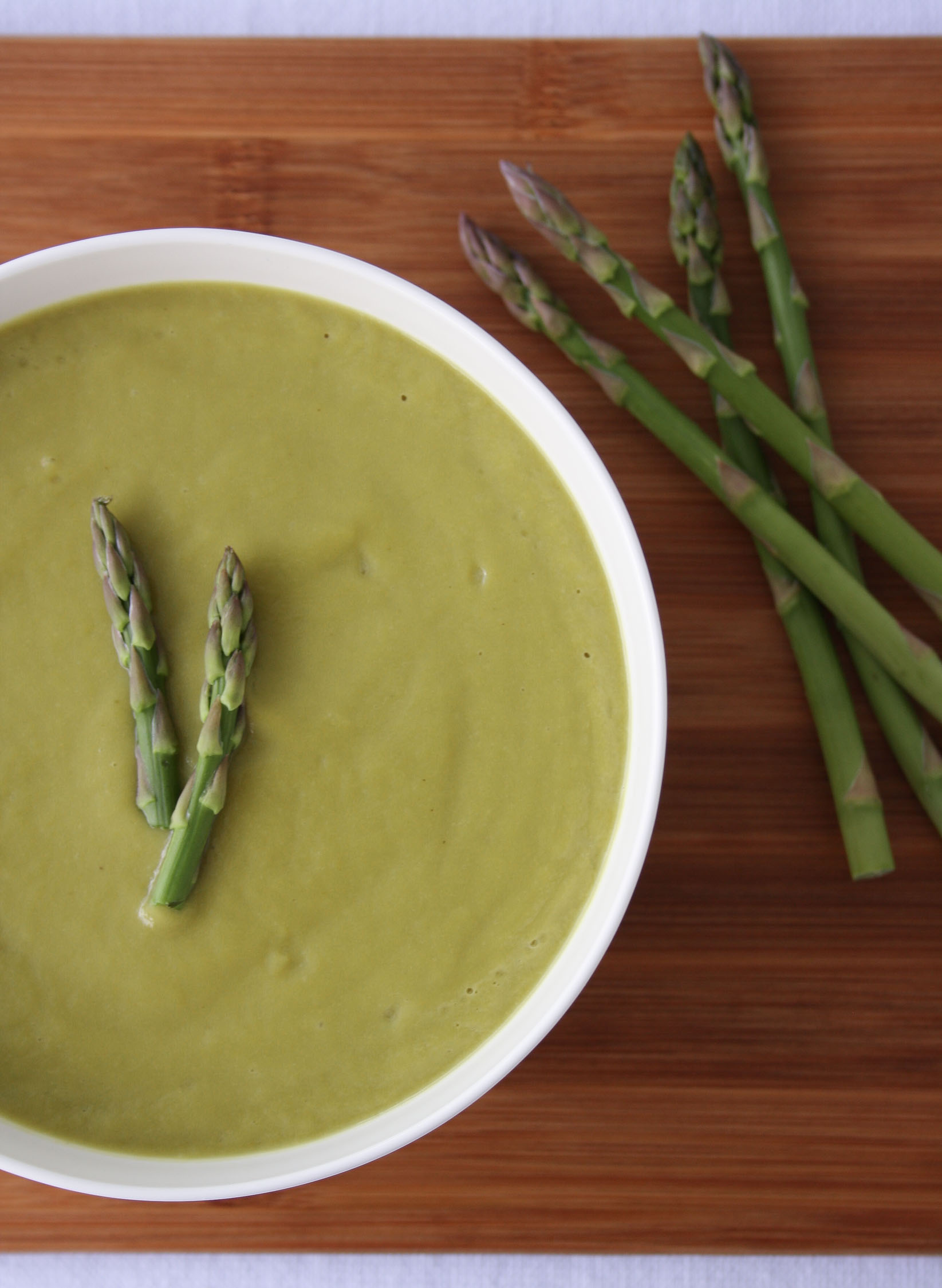 asparagus vichyssoise in a white bowl with four asparagus on the side