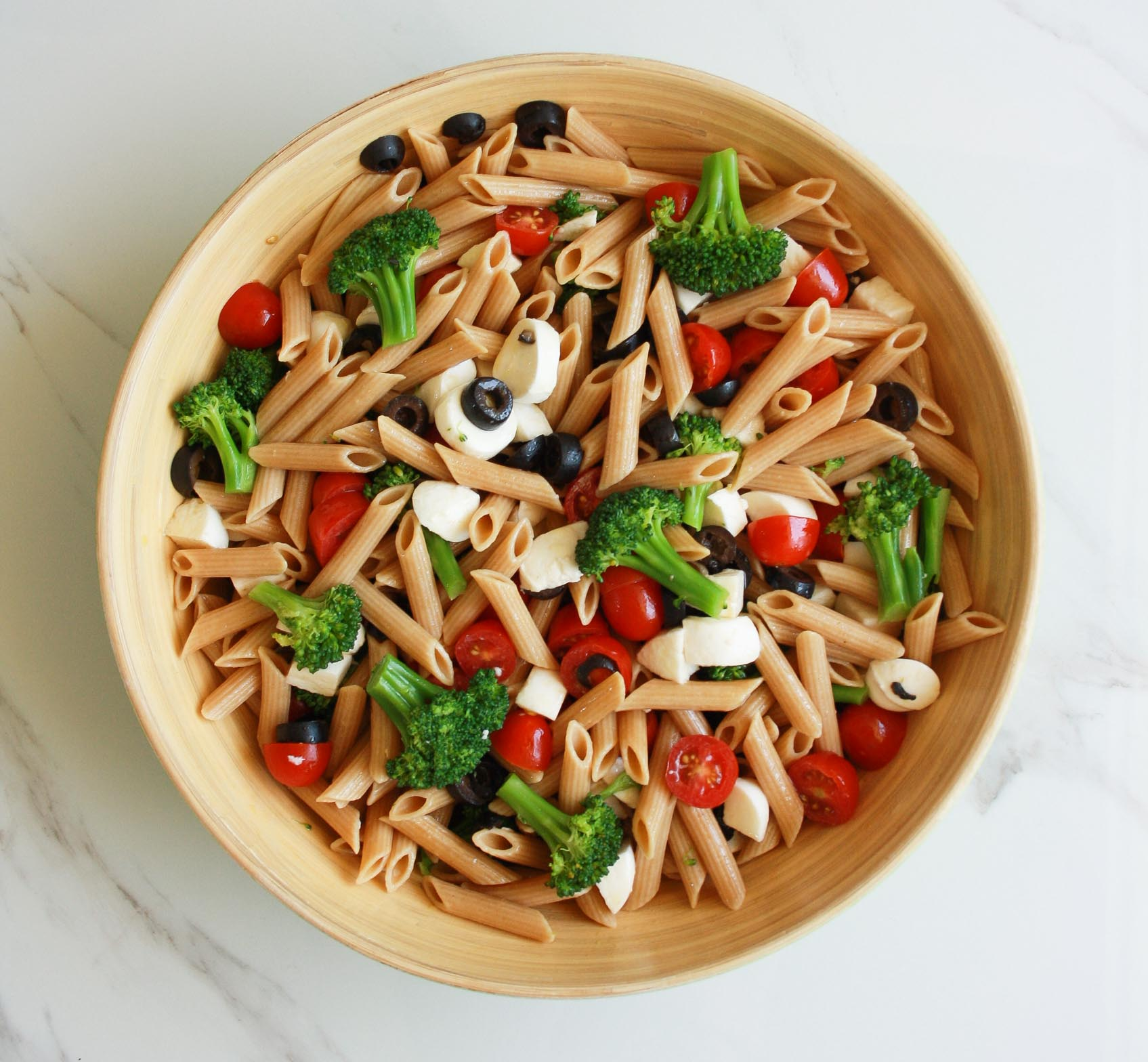Whole wheat penne pasta salad in a big bowl with tomatoes, broccoli, mozzarella and black olives