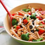 Whole wheat penne pasta salad in a big bowl with tomatoes, broccoli, mozzarella and black olives with red spoon