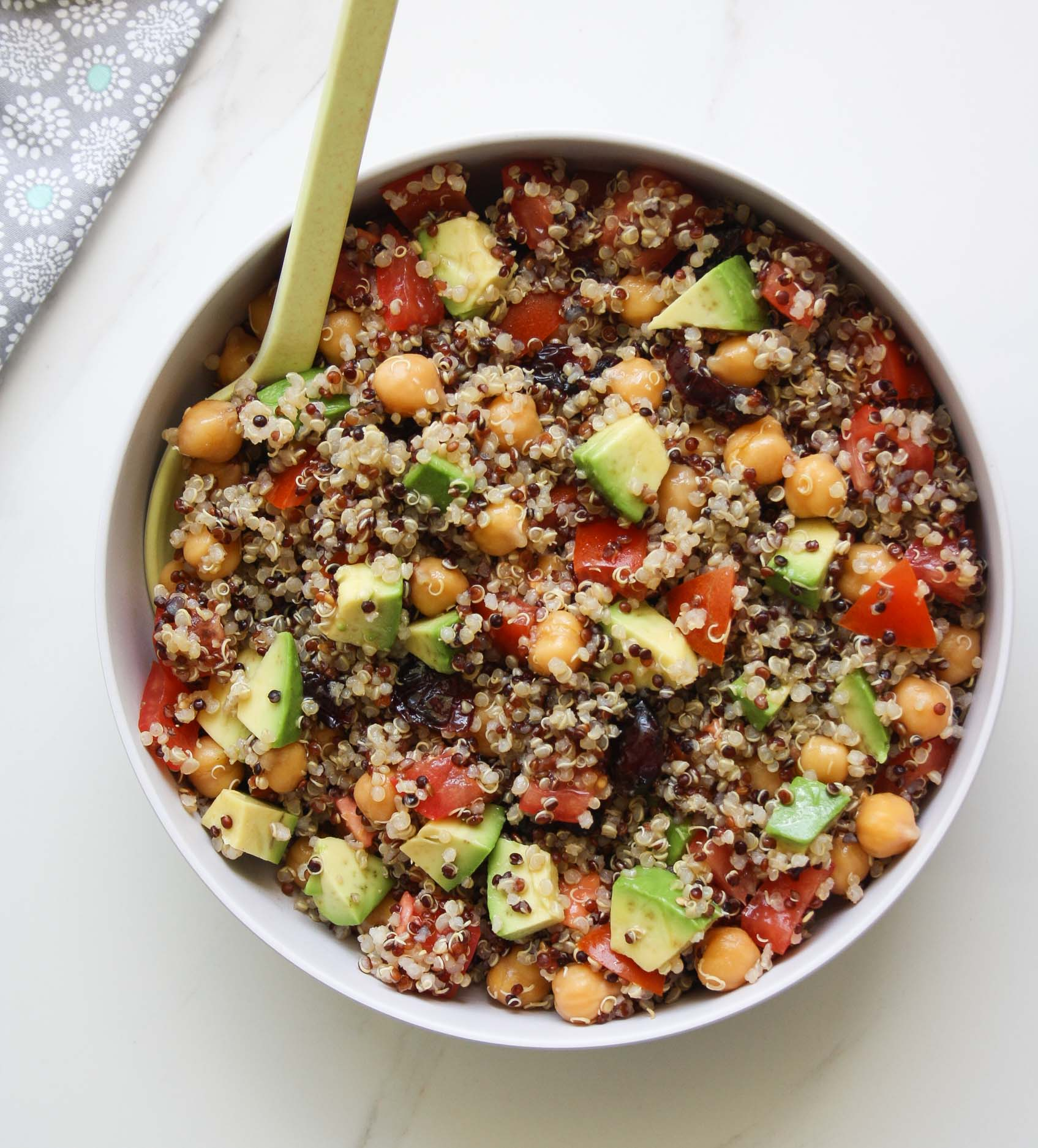 quinoa salad with avocado, tomatoes, chickpeas and cranberries with a spoon