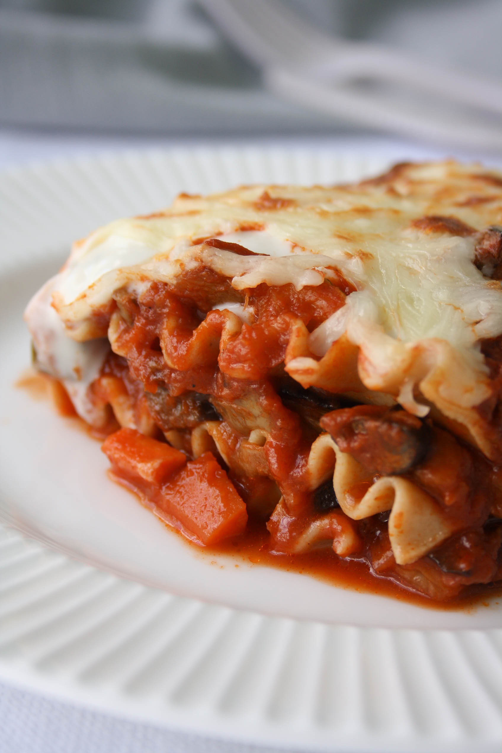 close up of the vegetable lasagna. layers of curly noodles with vegetables in tomato sauce and cheese and white sauce on top