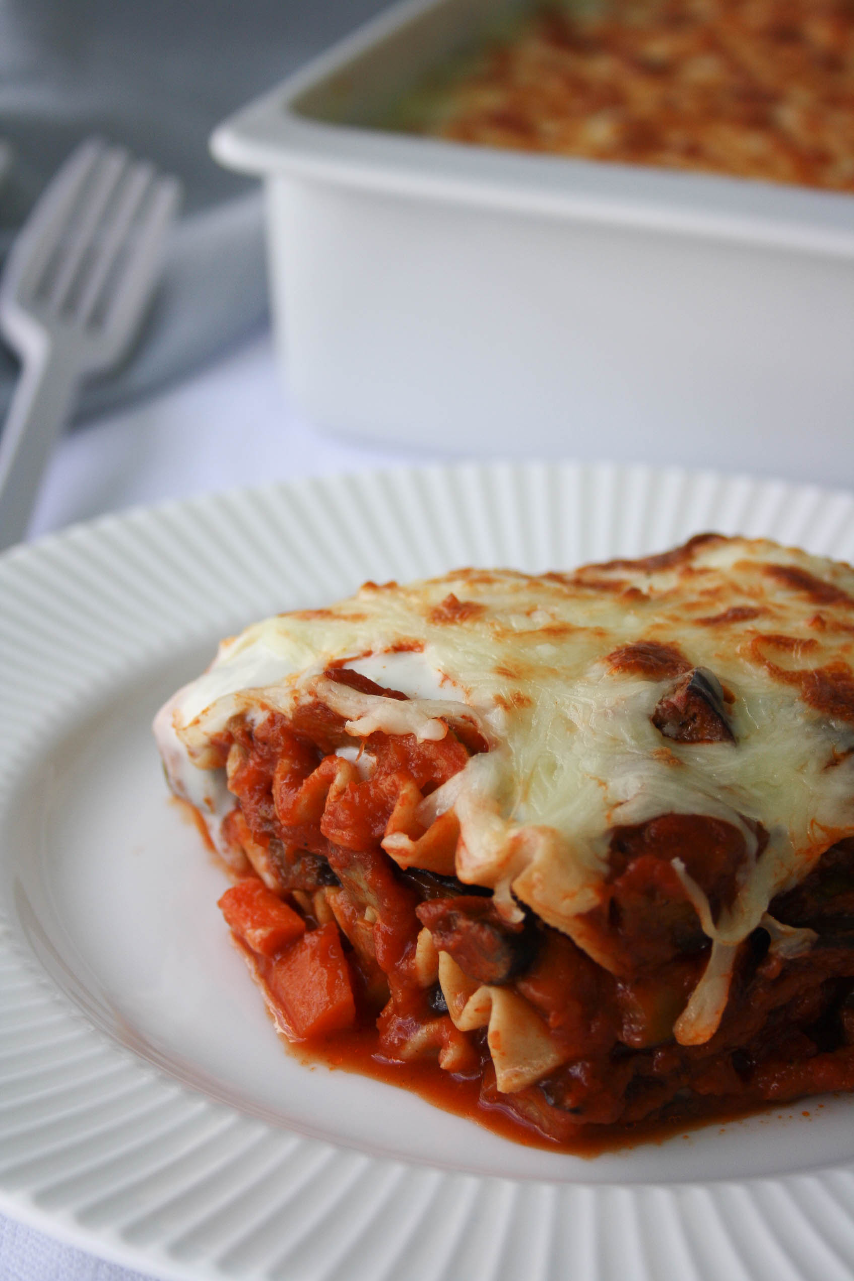 piece of lasagna in a plate. Whole wheat noodles with vegetables in tomato sauce and cheese and bechamel sauce on top