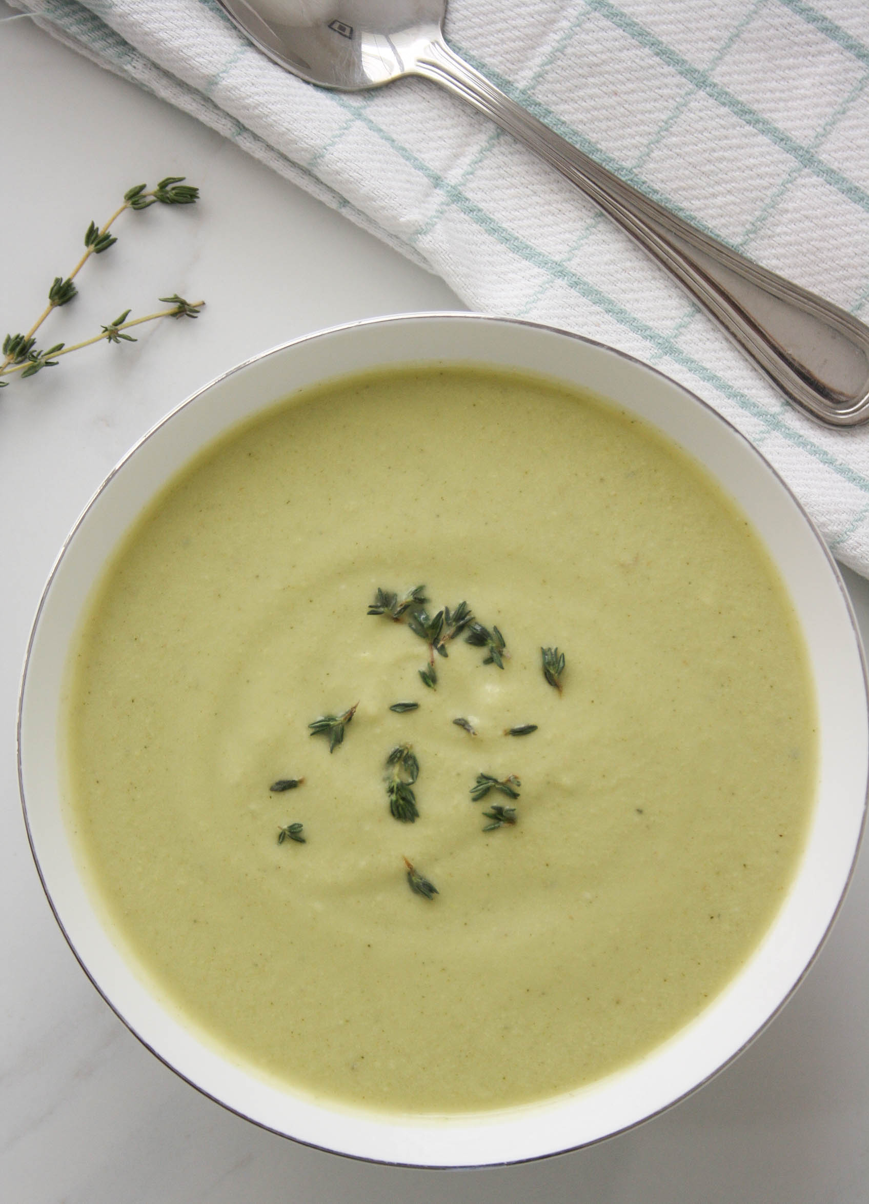 zucchini, cashew, thyme soup in a white bowl with a spoon on the side