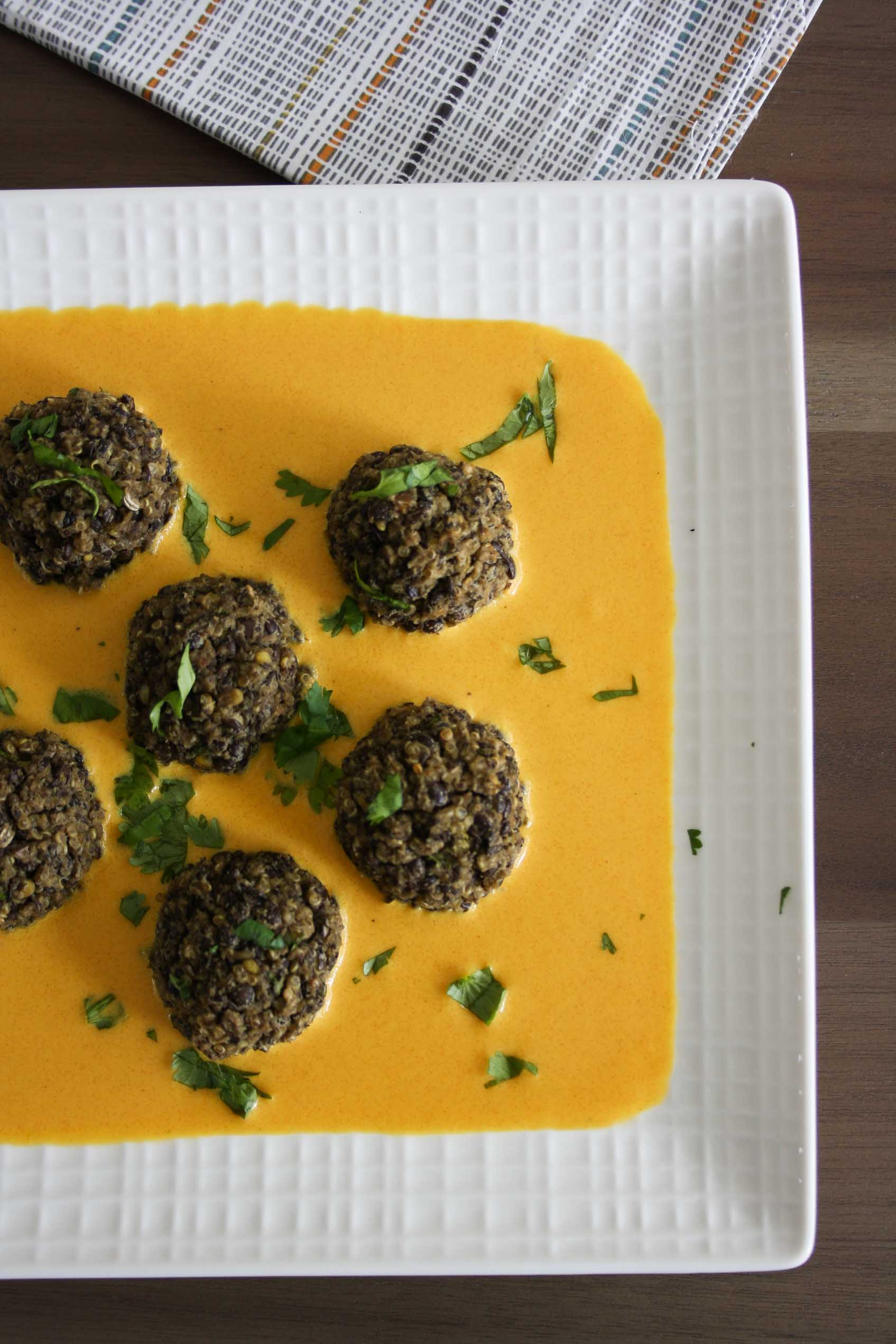 lentil and quinoa meatballs on top of curry sauce in a square white plate