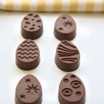 six chocolate shaped eggs with patterns on top