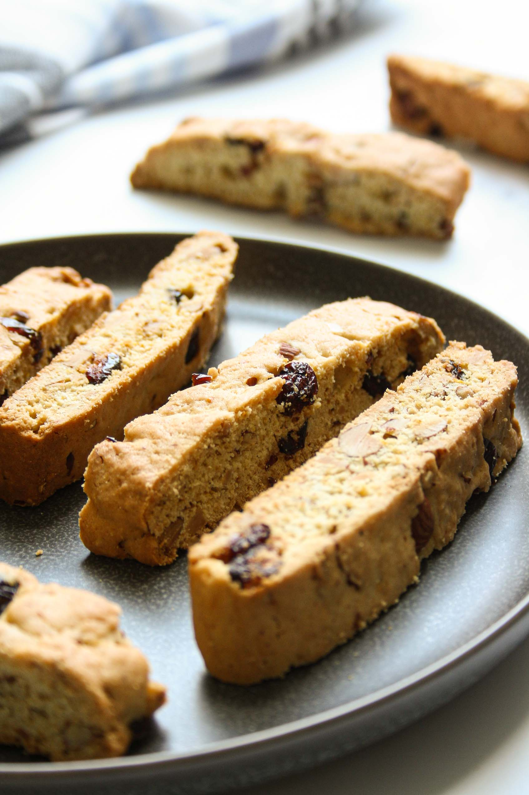 close up of cranberry almond biscotti on a dark grey plate