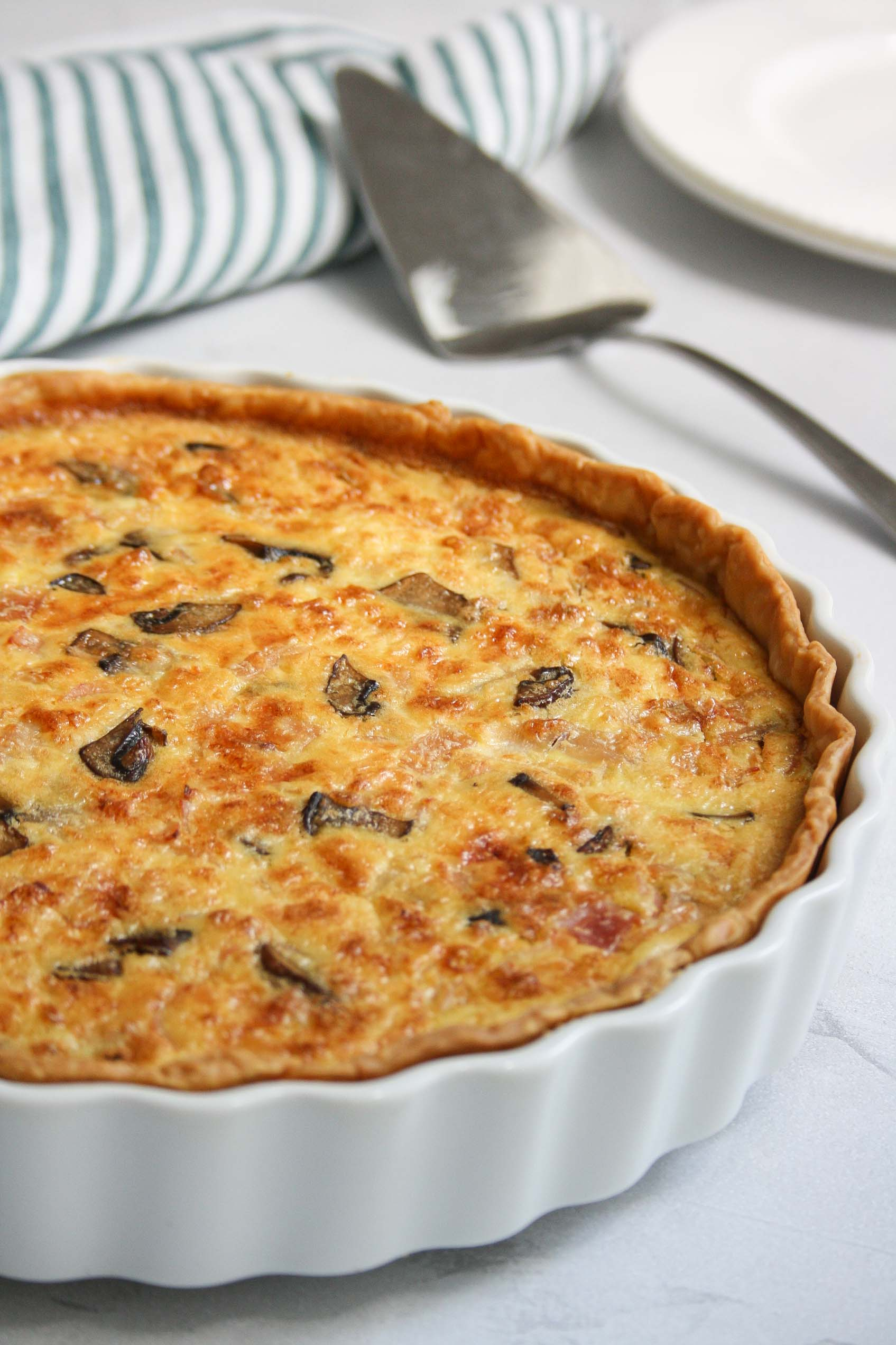 ham and mushroom quiche in a white pan with a cloth, serving spoon and plates on the background