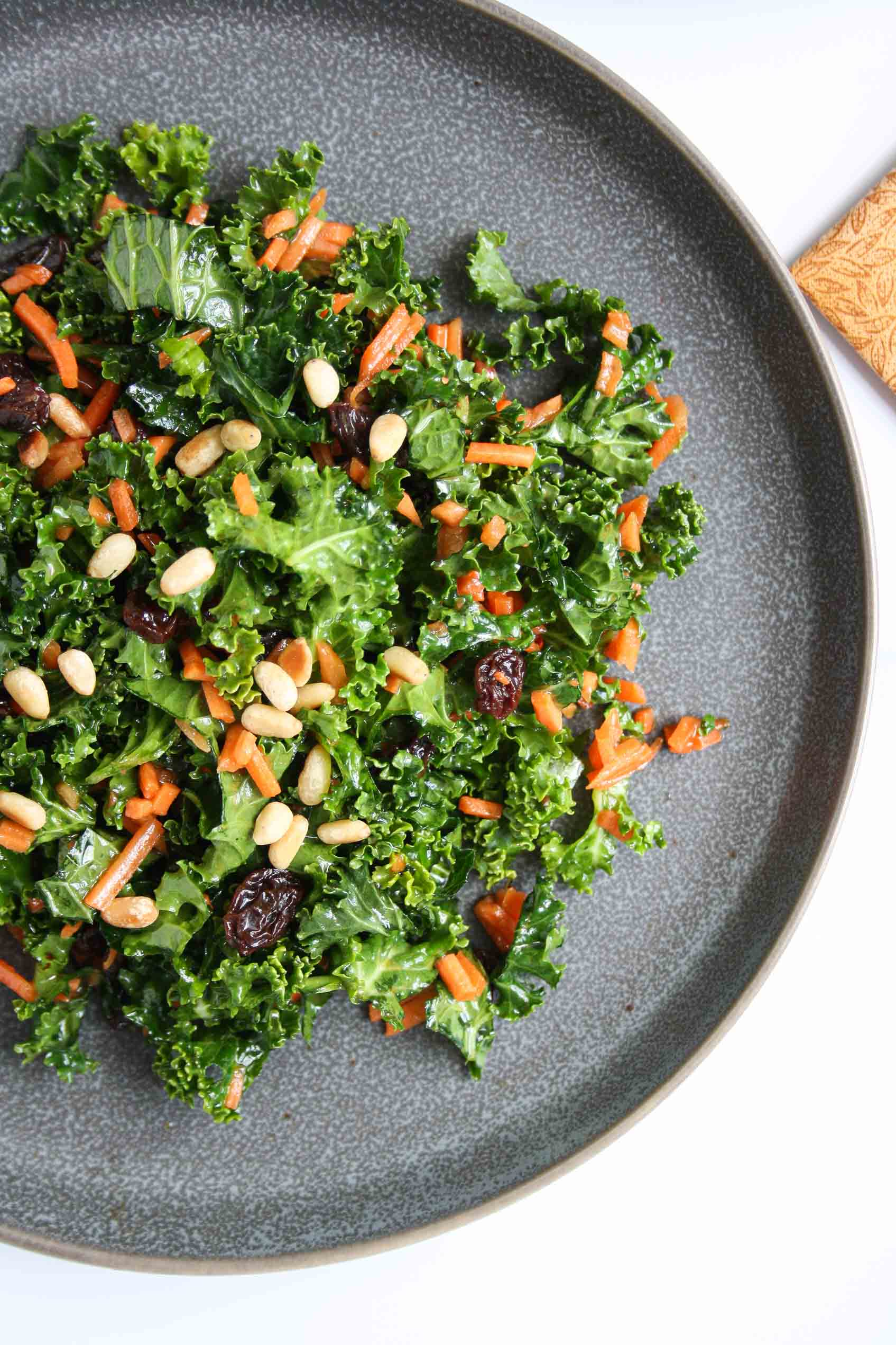 view from above of a carrot raisin pine nuts kale salad on a dark grey plate