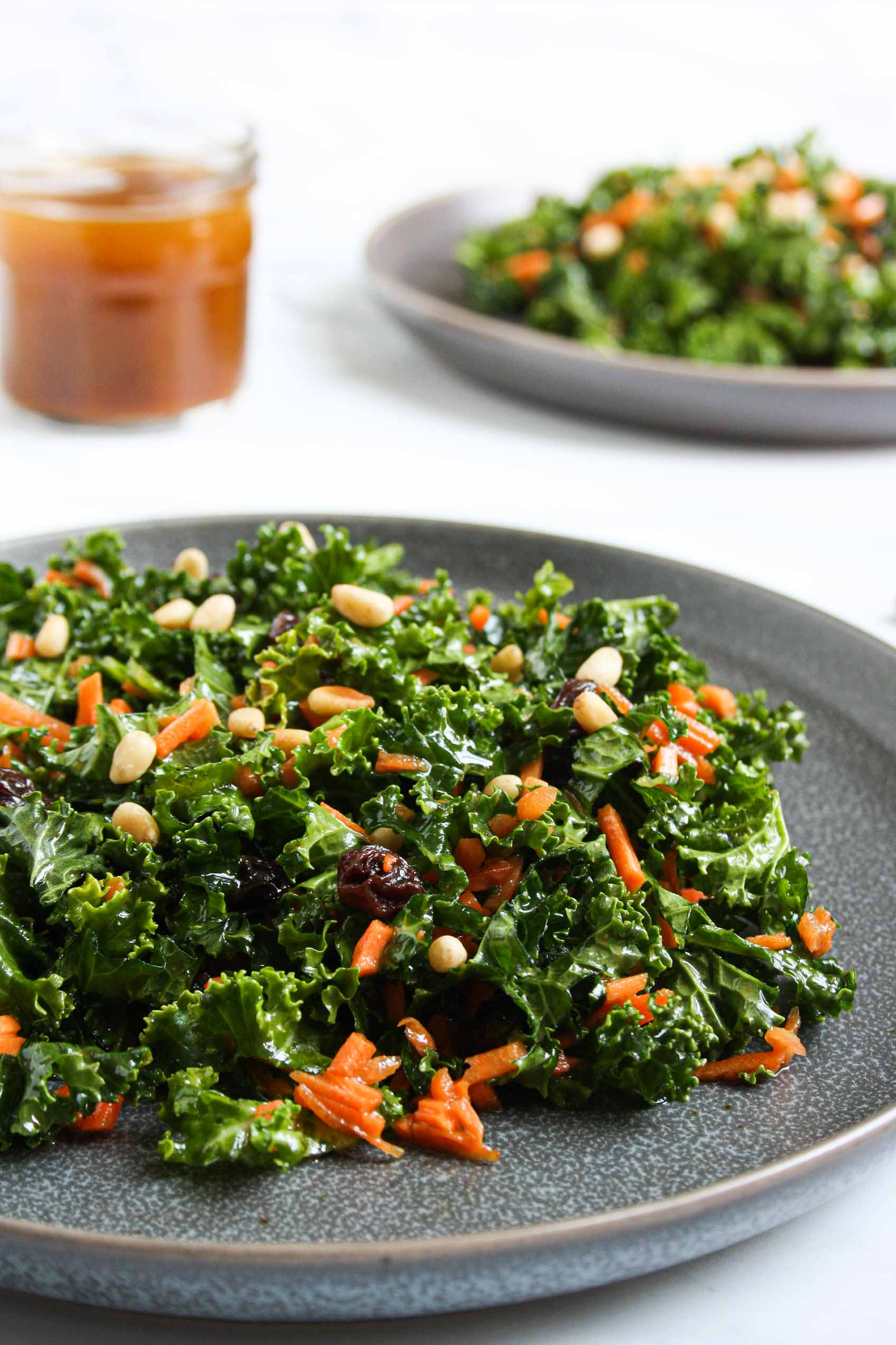 side view of a carrot raisin pine nuts kale salad on a dark grey plate