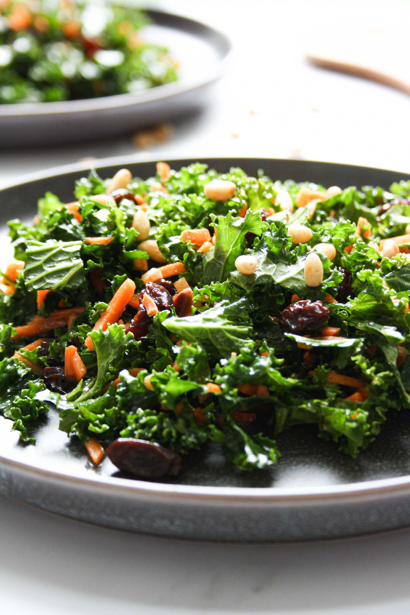 close up side view of a carrot raisin pine nuts kale salad on a dark grey plate