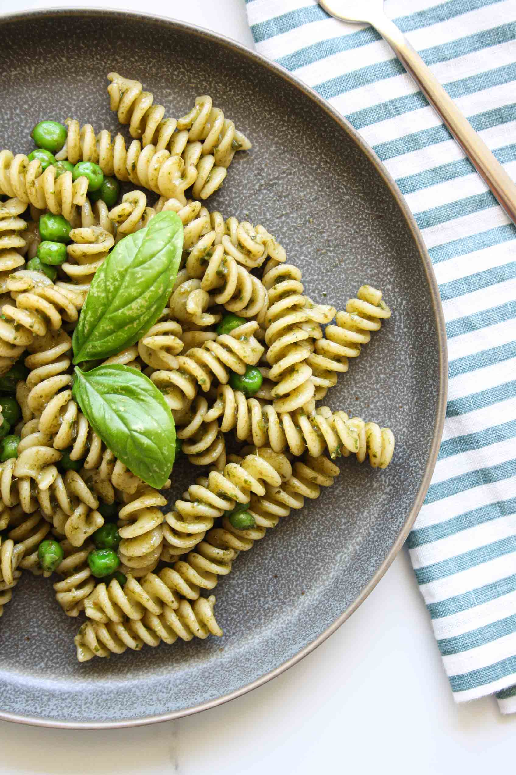 fusilli with no nut pesto and peas on a grey plate