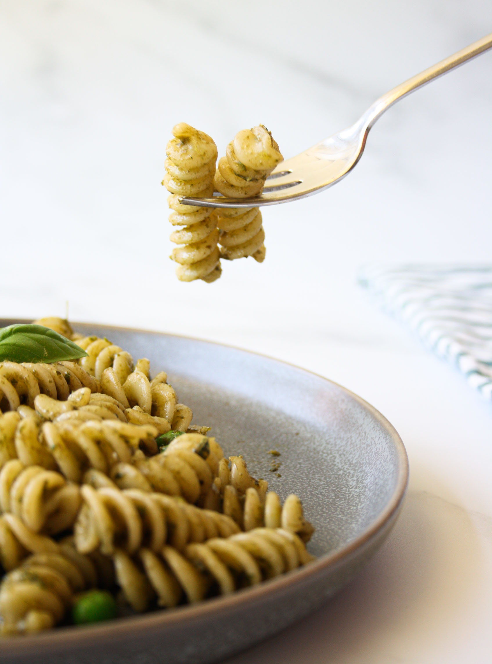 two fusilli with pesto pinched on a fork over a fusilli plate