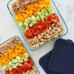 white beans, tomatoes, cucumber, yellow pepper and tuna salad arranged in two glass rectangular containers with blue lids on the side