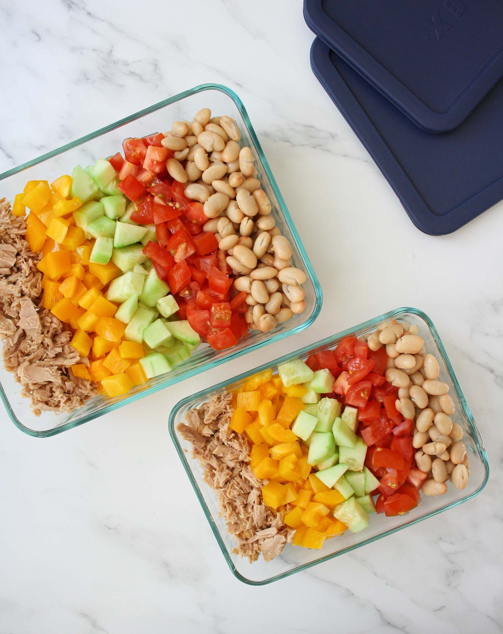 white beans, tomatoes, cucumber, yellow pepper and tuna salad arranged in two glass rectangular containers