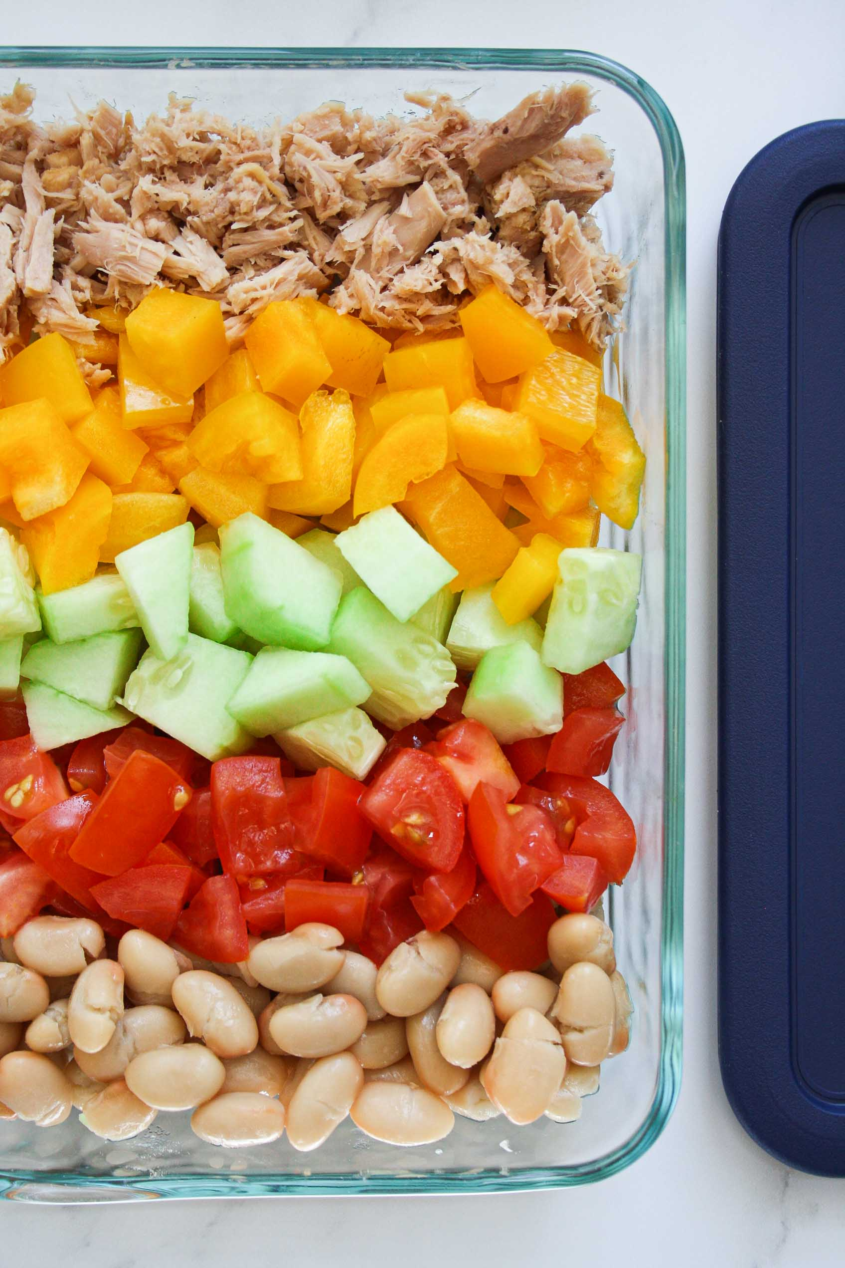 white beans, tomatoes, cucumber, yellow pepper and tuna salad arranged in a glass rectangular container