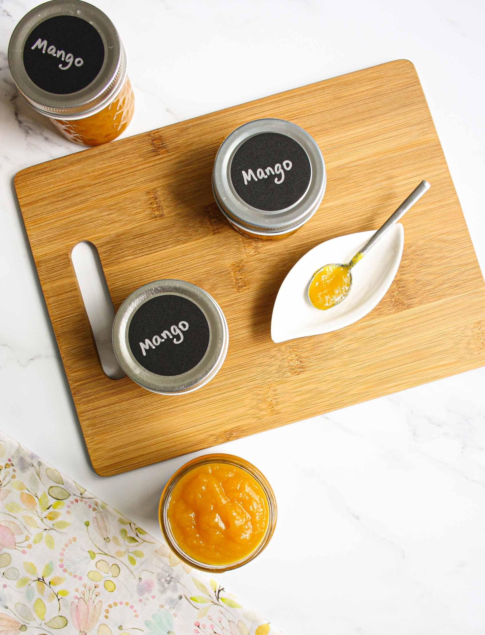 view from above of mango jam in a jar and different jars with lid on and a spoon with jam