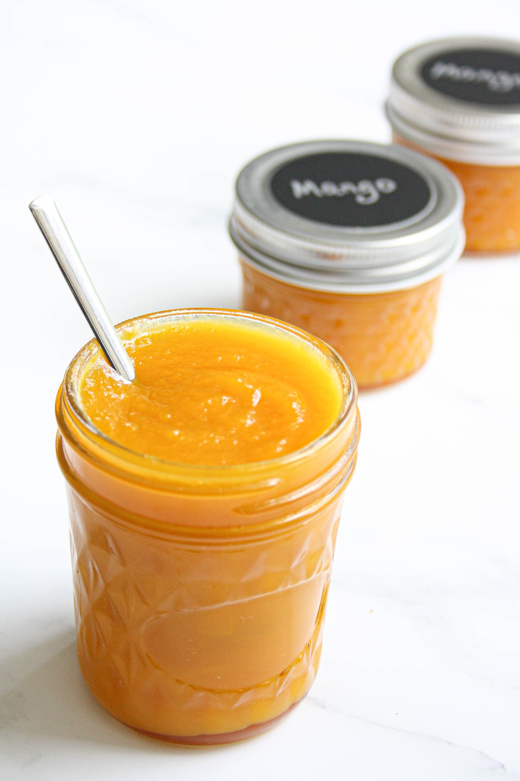 mango jam in a jar with a spoon in