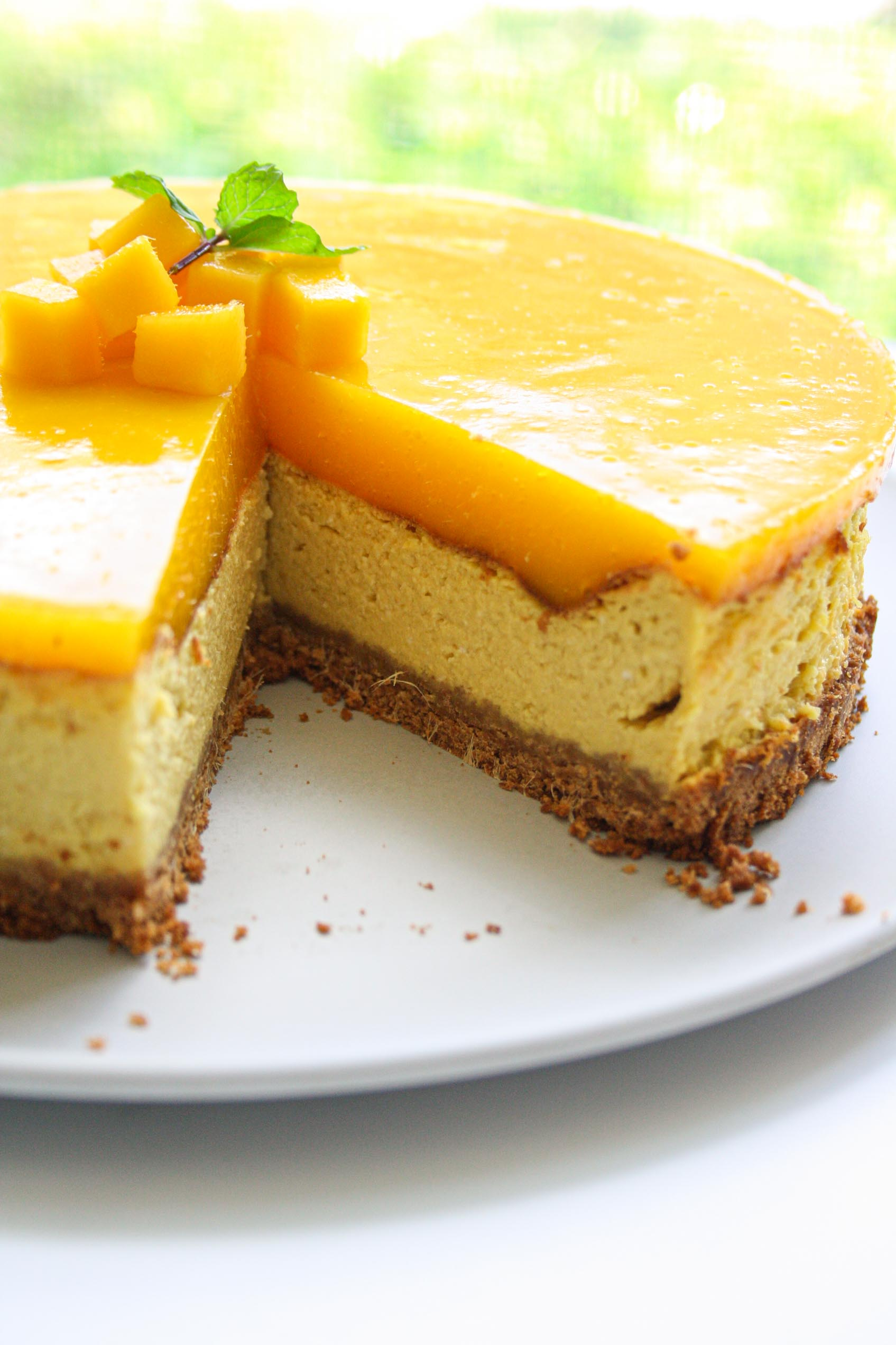 view from the side of a mango cheesecake with a cut out slice