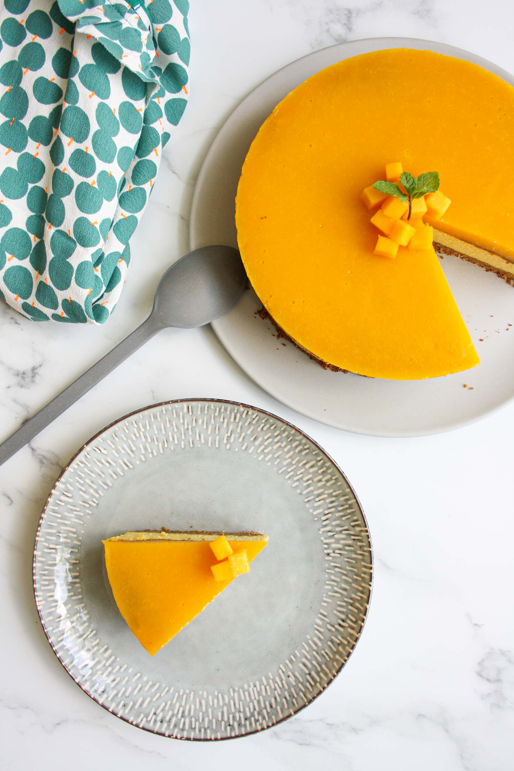 view from above of a mango cheesecake with a slice on a separate plate