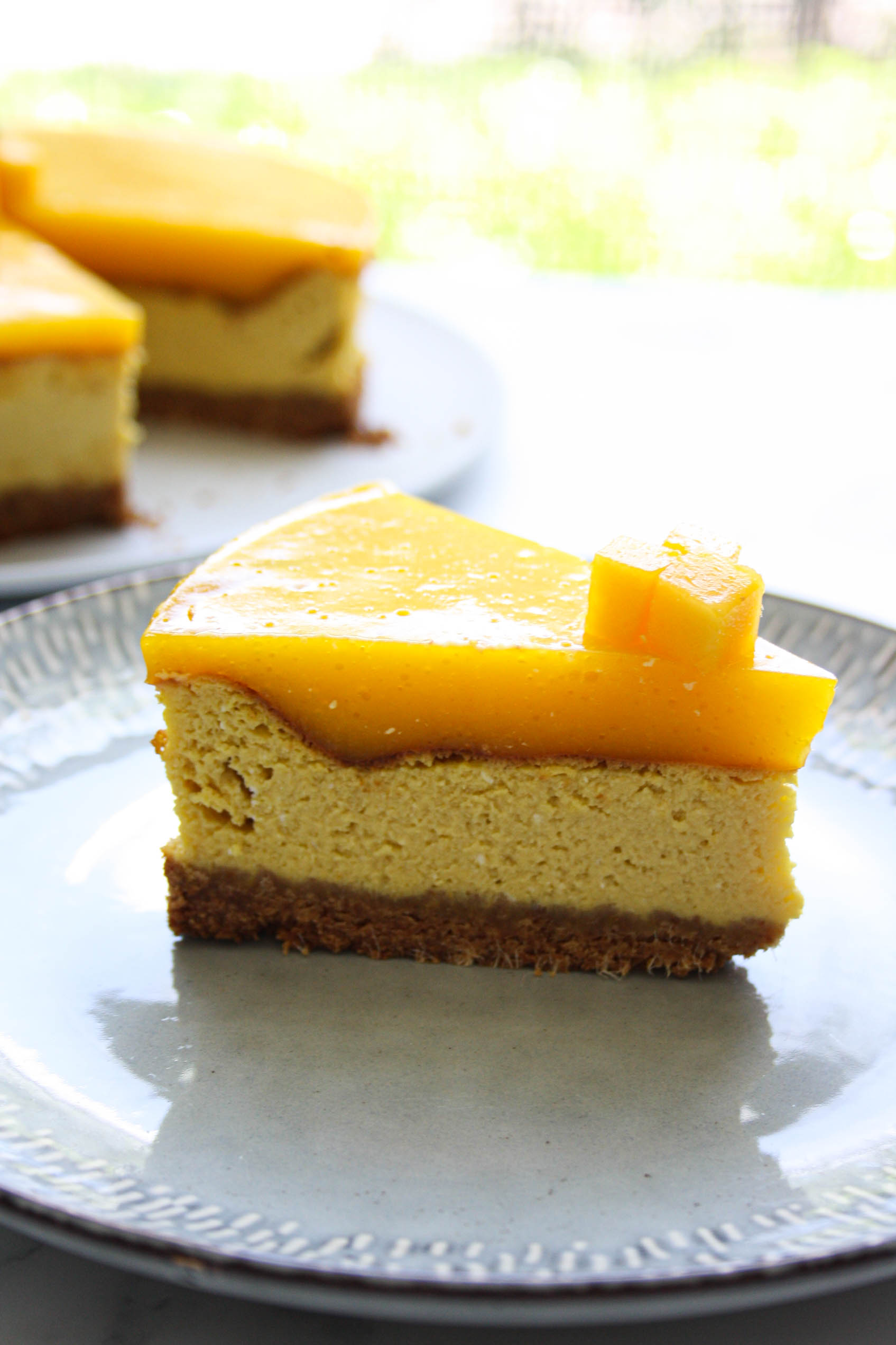detail of a slice of mango cheesecake from the side