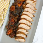 grey rectangular tray with sliced pork tenderloin with prunes, apricots and raisins on the side